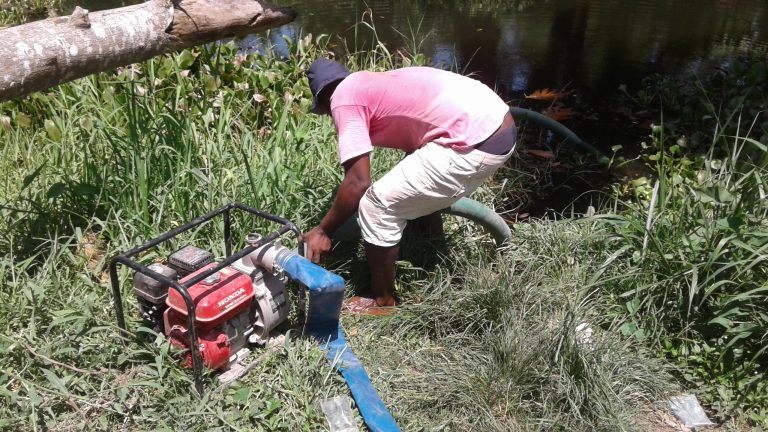 A farmer connecting the irrigation pump to a river